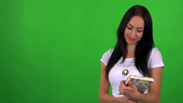 Cover Image for Young Pretty Woman Holds Book and Smiles - Green Screen - Studio