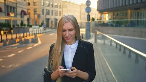 Formal Business Woman Walking on Street. Elegant Blond Girl in Suit and Walking on Street and