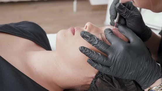 Young, Blonde Caucasian Woman Having Her Eyebrow Tattoo Removed
