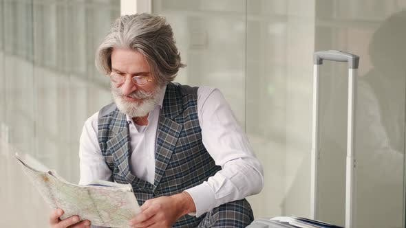 Senior Man Planning Vacation with a Map Sitting at the Airport