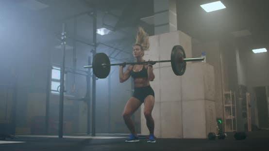 Thumbnail for Ein Weiblicher Gewichtheber führt einen Langhantellift in einer dunklen Turnhalle durch. Eine Frau, die einen schweren Stab über sie hebt