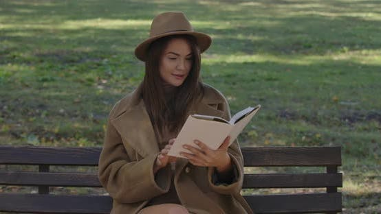 Thumbnail for Cute Caucasian Female Student in Elegant Brown Clothes Sitting on the Bench and Turning Book Pages