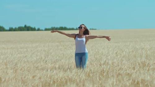 Nice Woman is Enjoying Life Walking in a Wheat Field