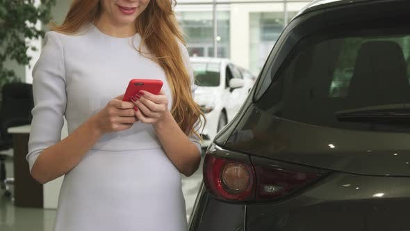 Thumbnail for Cropped Shot of a Cheerful Woman Using Smart Phone Standing Near Her Car