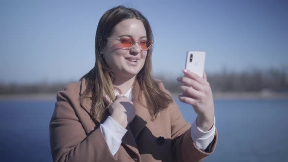 Cover Image for Close-up of Joyful Young Woman in Sunglasses Talking at Selfie Camera on Smartphone Outdoors