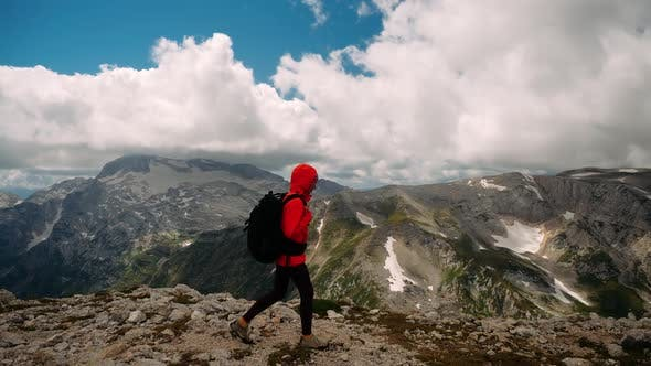 Thumbnail for Side View of Woman Walking Tourist Conquered and Climbed Peak in Orange Jacket and Backpack