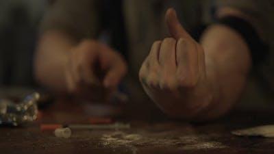 Hand of Depressed Man Making Drug Injection With Syringe at Abandoned Place