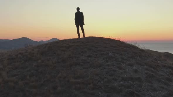 Thumbnail for A Man in a Suit Stands on Top of a Hill and Looks at the Dawn Over the Sea