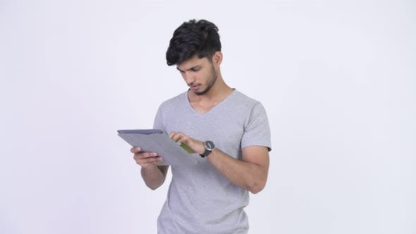 Thumbnail for Young Happy Bearded Indian Man Using Digital Tablet and Getting Good News