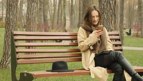 Woman with mobile phone sitting on bench in park and scrolling social network websites online