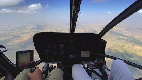 Innenansicht eines Hubschraubers im Flug mit Pilot und Mann, der an einem sonnigen Tag einen Hubschrauber fliegt