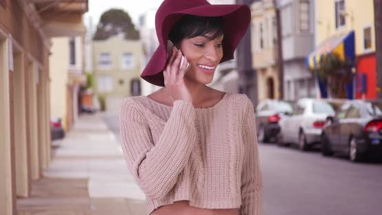 Thumbnail for Happy smiling black woman in floppy hat talking on smart phone in San Francisco