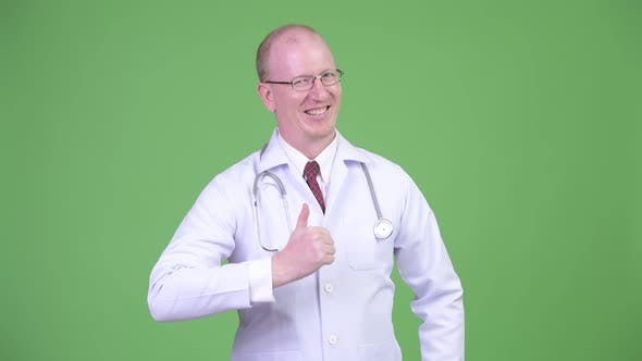 Thumbnail for Happy Mature Bald Man Doctor Giving Thumbs Up