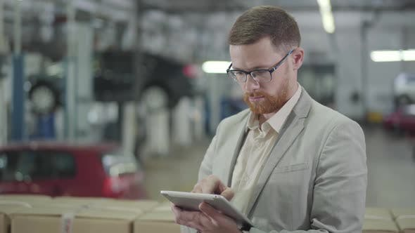 Thumbnail for Young Confident Caucasian Salesman Using Tablet, Looking at Camera and Gesturing Yes By Shaking Head