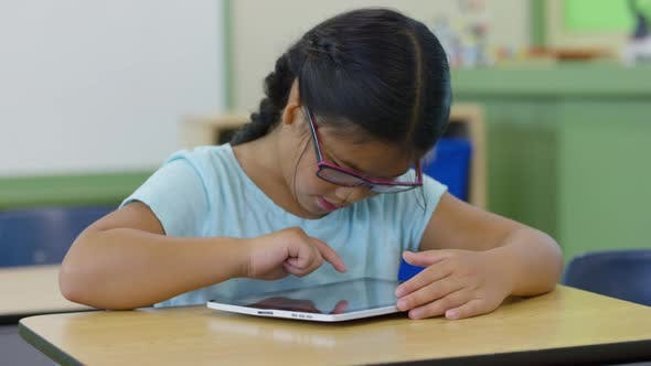 Young girl in school classroom using digital tablet