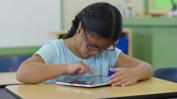 Young girl in school classroom using digital tablet
