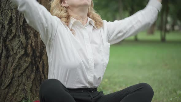 Thumbnail for Unrecognizable Caucasian Blond Businesswoman Sitting in Lotus Pose on Summer Meadow in Park