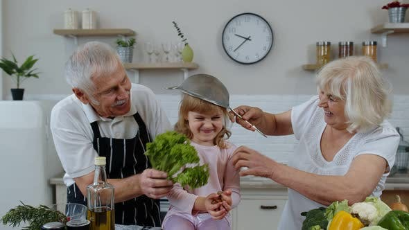 Thumbnail for Happy Vegan Senior Couple Dancing with Granddaughter Child While Cooking Vegetables in Kitchen