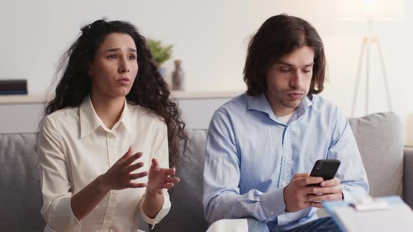 Emotional Stressed Woman Talking to Marital Counselor Annoyed Man Browsing on Smartphone Slow Motion