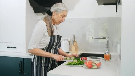 Thumbnail for Elderly Woman Chopping Salad Kitchen