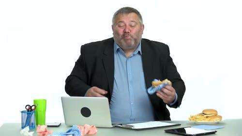 Businessman Enjoying Burger While Sitting at Desktop at Office