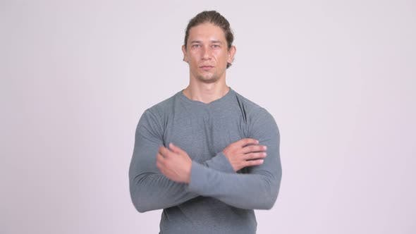 Thumbnail for Handsome Man with Arms Crossed Against White Background