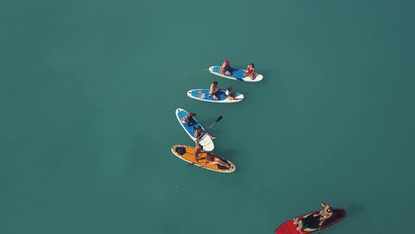 Young people doing standup paddleboarding