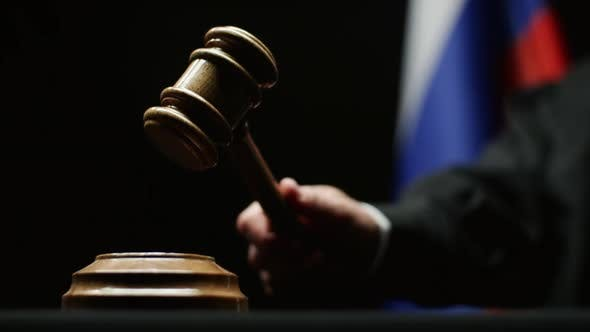 Thumbnail for Judge With Gavel In His Hand Hammering Against Russian Flag And Black Background In Courtroom