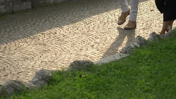 A man and woman couple walking on a cobblestone street, Italy, Europe.