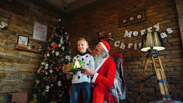 Thumbnail for Curious Male Child Receives Gift From Santa Claus in Decorated Festive Room