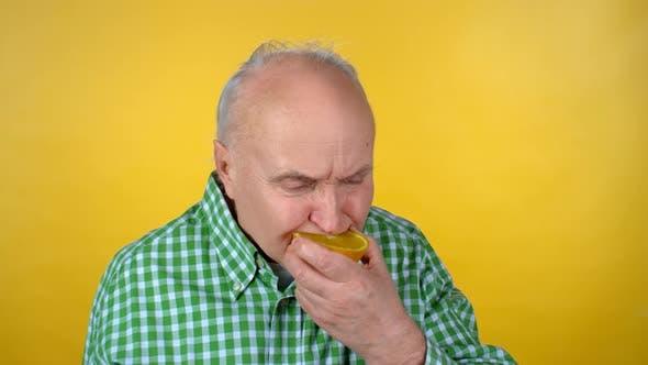Thumbnail for Elderly Man Biting Orange