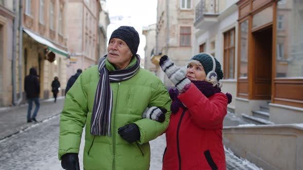 Thumbnail for Senior Old Couple Grandmother and Grandfather in Colorful Winter Jackets Walking in Winter City