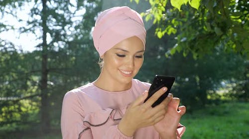 Beautiful Muslim Woman in Turban with Phone on Background of Trees