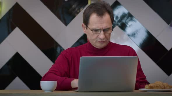Handsome Middleaged Man Working with Laptop in Cafe