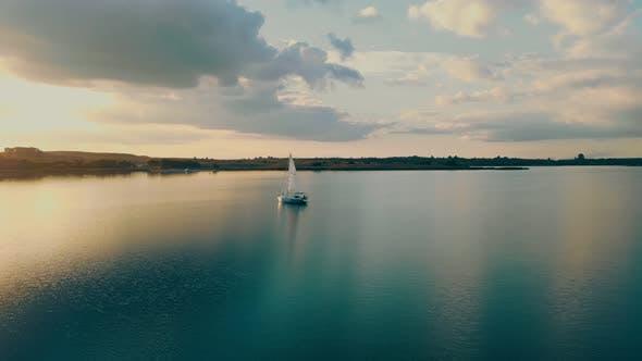 Luftaufnahme Eine Yacht bei Sonnenuntergang im offenen Meer. Flug bei Sonnenuntergang in der Nähe der Yacht mit Segel Blick
