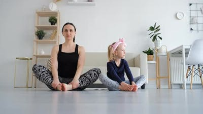 Mother with Daughter Practicing Yoga at Home