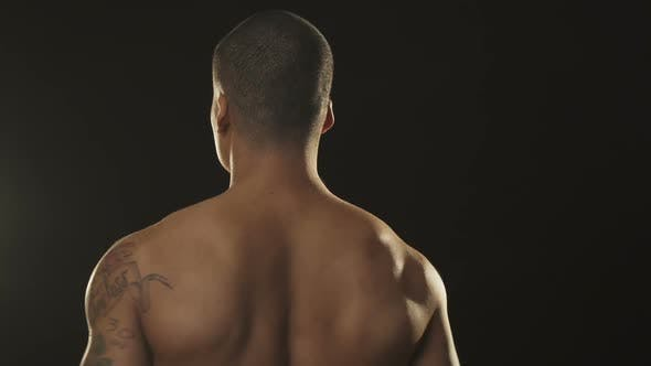 Thumbnail for Rearview Shot of a Muscular Athletic African Man Warming Up