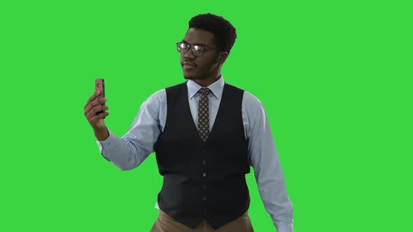 Thumbnail for African American Businessman Making Selfies with His Phone While Walking on a Green Screen, Chroma