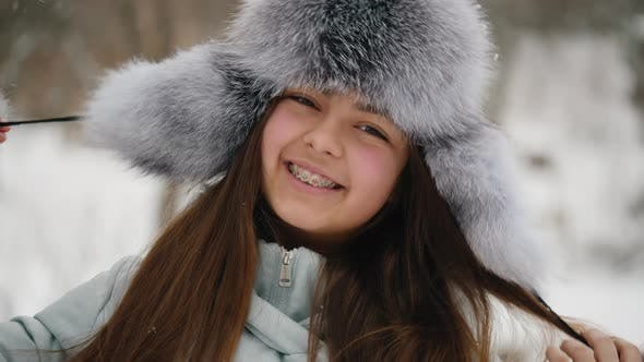 Winter Portrait of a Cheerful Teenage Girl in a Fur Hat