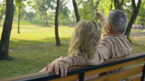 Senior Couple Sitting on Bench, Watching Tourist Attraction Afar, Travel