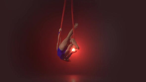 Beautiful Aerialist Girl Doing Acrobatic and Flexible Tricks on Red Aerial Silks Tissues on Red