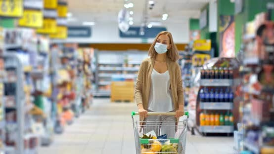 Young Woman Carries a Cart with Groceries in the Supermarket, Shopping for Groceries During the