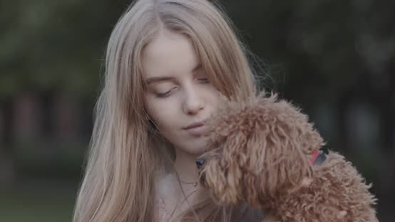 Thumbnail for Beautiful young girl holding a dog in her arms