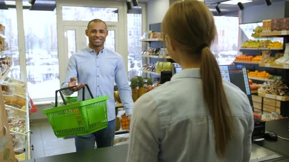 Male Customer Paying with Credit Card To Cashier