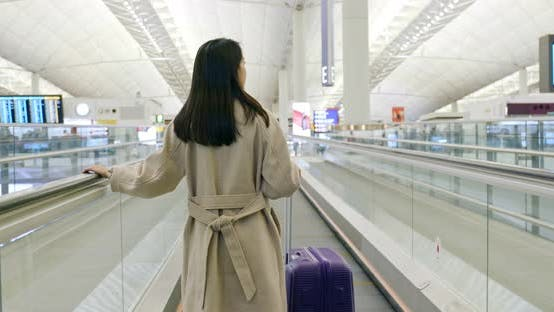 Thumbnail for Back View of Businesswoman on Travelator with Her Luggage at Airport