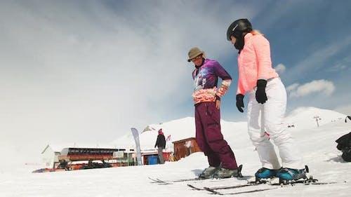 Hipster Caucasian Ski Intsructors Teach Female Beginner Skier To Ski