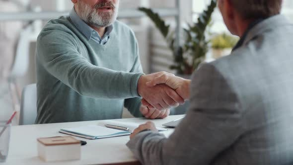 Senior Man Shaking Hands and Speaking with Business Associate in Office