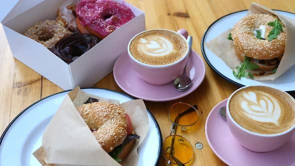 Trendiges Frühstück mit Bagels, Donuts und Kaffee auf Holztisch