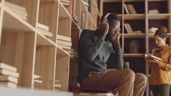 Young Black Man Putting on Headphones and Using Smartphone in Book Cafe
