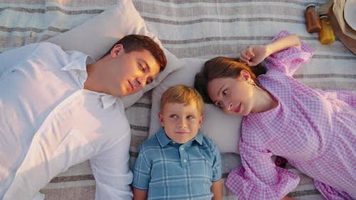 Family with Child Relaxing on Blanket at Sunset